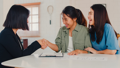 Asian Lesbian lgbtq women couple sign contract at home, Young couple consulting with real estate financial advisor, Buying new house and handshaking with broker in living room concept.